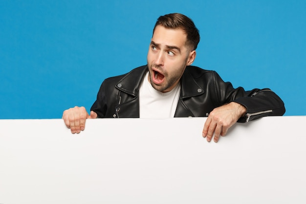 Knappe jonge bebaarde man houdt grote witte lege lege billboard voor promotionele inhoud geïsoleerd op blauwe muur achtergrond studio portret. mensen oprechte emoties levensstijl concept. bespotten kopie ruimte.