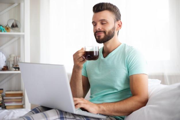 Knappe jonge bebaarde man in casual kleding werkt thuis zittend op het bed. zelfverzekerde man met een laptop en smartphone drinkt koffie in de slaapkamer.