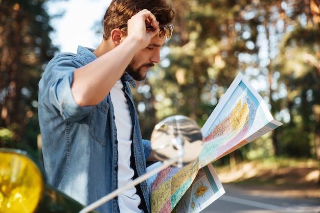 Knappe jonge bebaarde man in de buurt van scooter kijken naar kaart