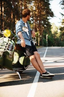 Knappe jonge bebaarde man permanent in de buurt van scooter buitenshuis