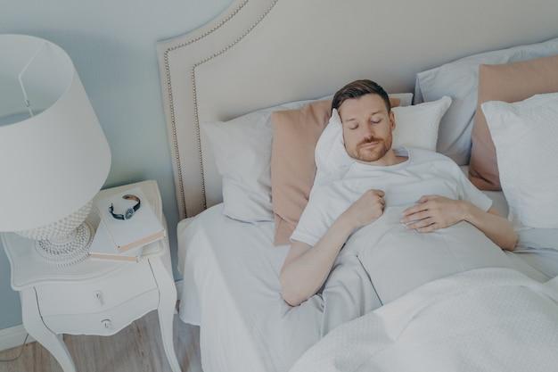 Knappe jonge bebaarde man rustig slapen in ruim comfortabel bed in de vroege ochtend thuis, man genieten van zoete dromen en ontspanning tijdens de nachtrust. uitzicht van boven