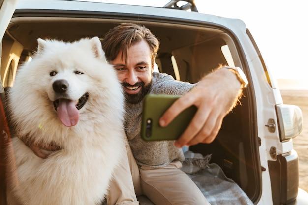 Knappe jonge bebaarde man zit achter in zijn auto, speelt met hond op het strand en maakt een selfie