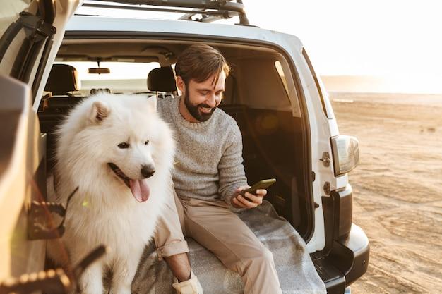 Knappe jonge bebaarde man zit achter in zijn auto, speelt met hond op het strand, met behulp van mobiele telefoon