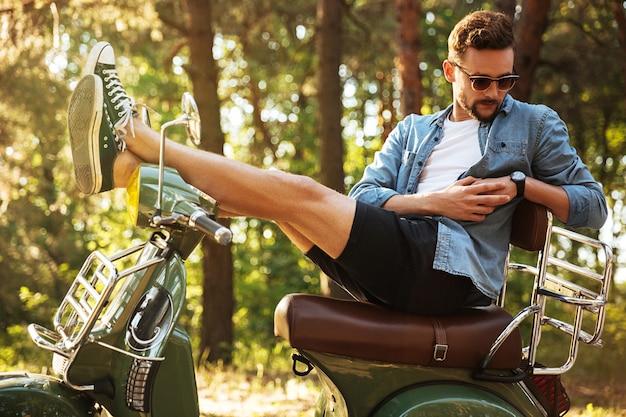 Knappe jonge bebaarde man zittend op scooter buitenshuis