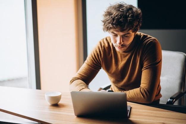 Knappe jonge bedrijfsmens die aan computer werkt en koffie drinkt