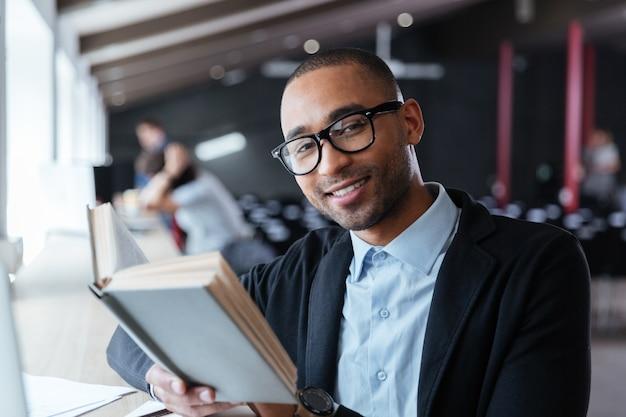 Knappe jonge bedrijfsmens die een boek leest aan zijn bureau op kantoor
