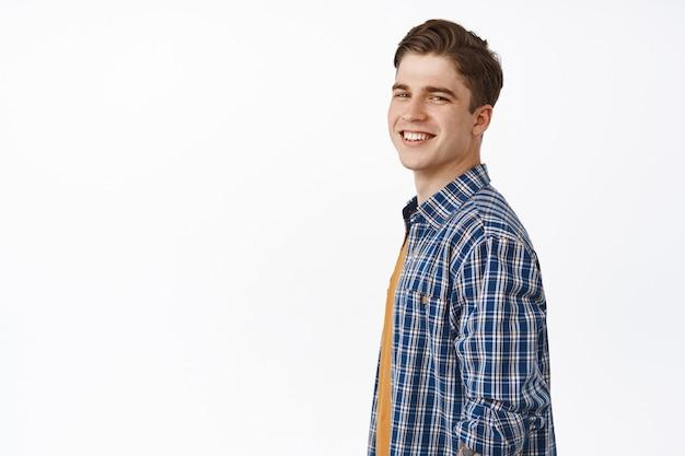 Knappe jonge blanke man die gelukkig en zorgeloos naar de camera kijkt, tevreden glimlacht, casual in zomeroutfit op wit staat