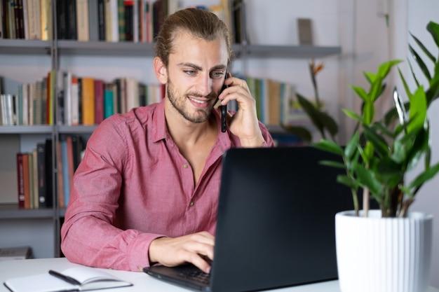 Knappe jonge blanke man met behulp van computer thuis werken en praten met mobiel gevoel gelukkig