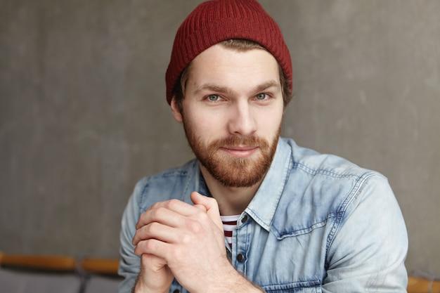 Knappe jonge blanke man met dikke baard op zoek met flirtende glimlach, handen gevouwen. aantrekkelijke man stijlvolle kleding dragen