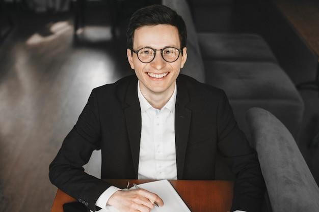 Knappe jonge blanke man met zonnebril kijken camera glimlachen terwijl hij een hand op zijn notebook.