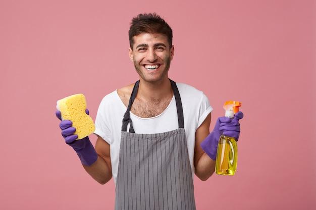Knappe jonge blanke man van de schoonmaakdienst klaar om je appartement op te ruimen tot het net zo netjes is als was, uitgerust met wasmiddel en spons, kijkt met een blije, vrolijke glimlach