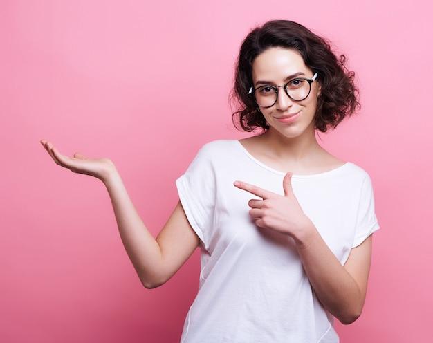 Knappe jonge blanke vrouw in ronde transparante eyewear, houdt hand omhoog