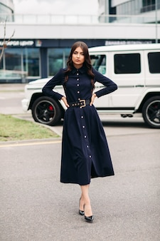 Knappe jonge blanke vrouw met mooi gezicht in een mooie zwarte jurk met een lengte onder de knie loopt naar de straat