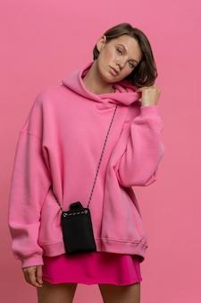 Knappe jonge blanke vrouw poseren in trendy roze oversized sportkostuum poseren