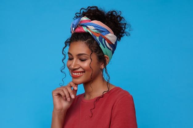 Knappe jonge blij donkerharige krullende vrouw die zachtjes haar kin aanraakt met opgeheven hand en mooi glimlacht, staande tegen blauwe muur in casual t-shirt