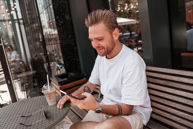 Knappe jonge blonde man zittend op café terras met koffiedrank glimlachend met mobiele smartphone op grote stad straat glas gebouw reflectie achtergrond. millennial hipster op zonnige zomerdag
