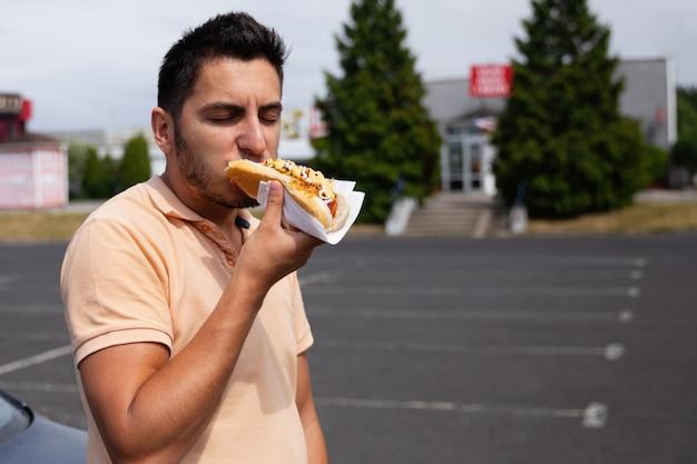 Knappe jonge donkerbruine mens die hotdog op het parkeerterrein dichtbij het benzinestation eet.