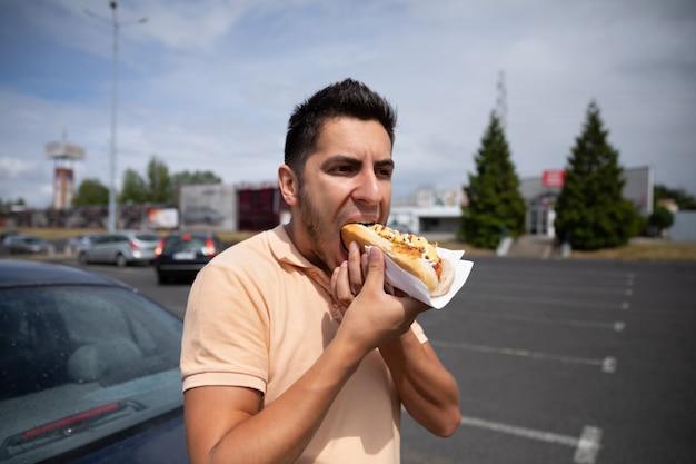 Knappe jonge donkerbruine mens die hotdog op het parkeerterrein eet dichtbij het benzinestation.
