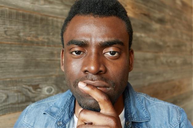 Knappe jonge donkere werknemer met stoppels houdt wijsvinger op zijn lippen en kijkt met een doordachte en geconcentreerde uitdrukking, nadenkend over het voorstel van zijn potentiële baas
