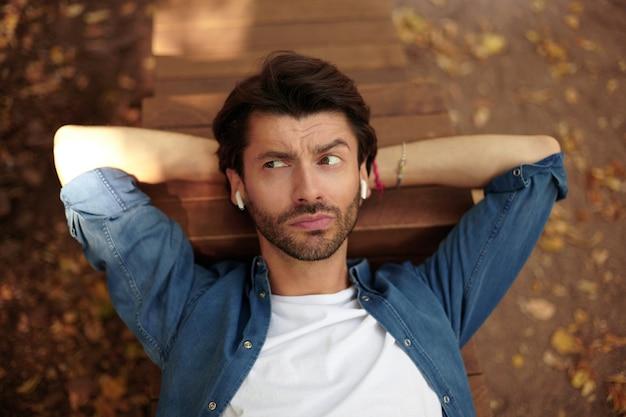 Knappe jonge donkerharige man opzij kijken met verbaasd gezicht, voorhoofd samentrekken en wenkbrauwen optrekken, liggend op de bank met de handen onder het hoofd