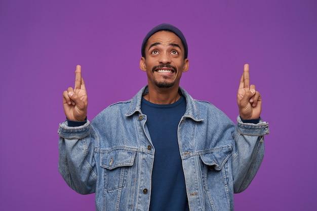 Knappe jonge donkerhuidige, bebaarde brunette man kijkt naar boven met grote hoop en bijt onderlip, wijsvingers omhoog houden terwijl poseren over paarse muur