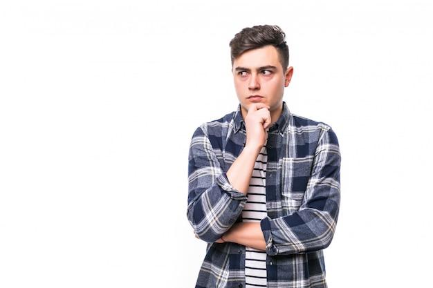 Knappe jonge doordachte man geïsoleerd over witte muur