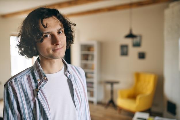 Knappe jonge europese kerel die alleen woont, de hele dag thuis doorbrengt terwijl hij sociaal afstand neemt, optimistisch en zorgeloos is, camera kijkt met een glimlach
