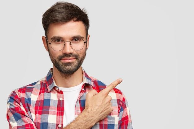 Knappe jonge europese man met haren, wijst naar de rechterbovenhoek met wijsvinger