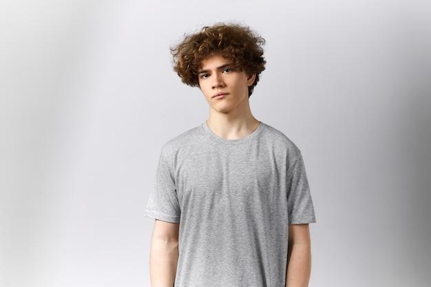 Knappe jonge europese man met leeg grijs t-shirt met kopie ruimte voor uw sjabloon, print of ontwerp, camera kijken met ernstige uitdrukking