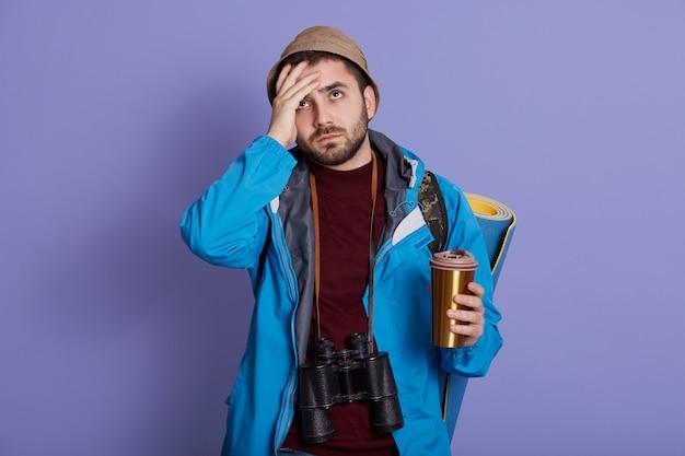 Knappe jonge europese mannelijke toerist met hoed en jas, met koffie meenemen in thermos mok, ziet er moe uit, houdt de hand op het voorhoofd