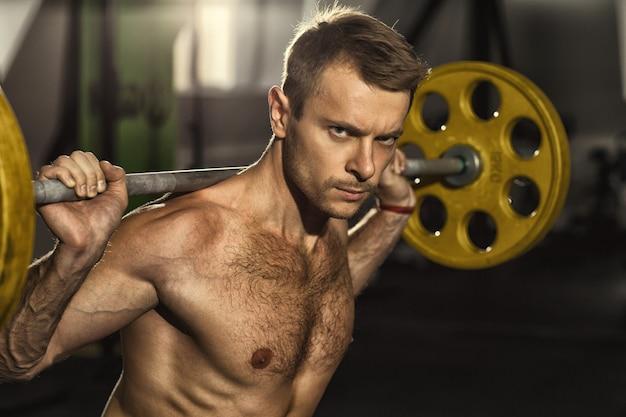 Knappe jonge fitness man uit te werken met een halter in de sportschool