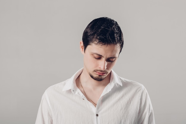 Knappe jonge gefrustreerde en haatdragende brunette man in wit overhemd op grijze achtergrond. zacht, licht