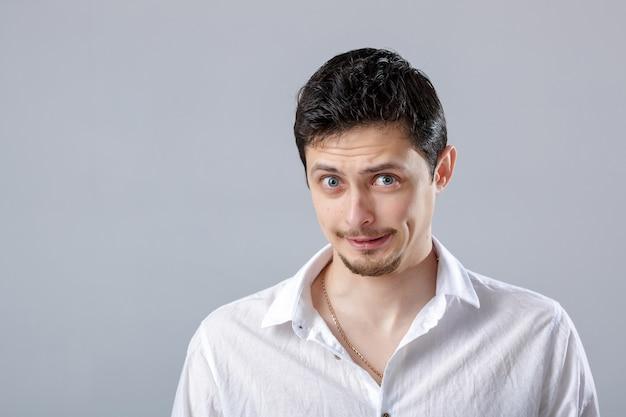 Knappe jonge gefrustreerde en haatdragende brunette man in wit overhemd op grijze achtergrond.
