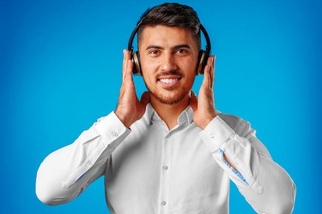 Knappe jonge gemengd ras man luisteren naar muziek met blauwe koptelefoon close-up