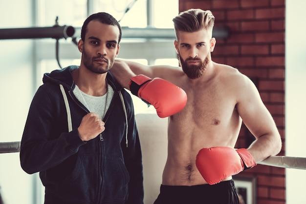 Knappe jonge gespierde boksers kijken naar de camera.