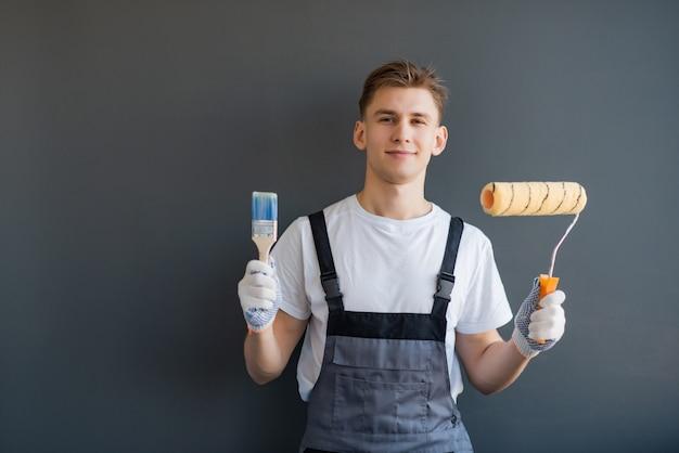 Knappe jonge glimlachende arbeider met verfrol en borstel op grijze achtergrond