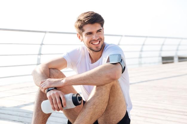 Knappe jonge glimlachende sportman die buiten een waterfles zit en vasthoudt
