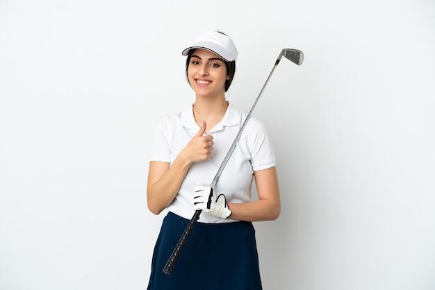 Knappe jonge golfer speler vrouw geïsoleerd op een witte achtergrond met een duim omhoog gebaar
