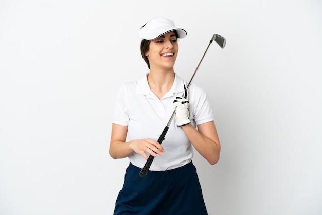 Knappe jonge golfer speler vrouw geïsoleerd op een witte achtergrond op zoek naar kant