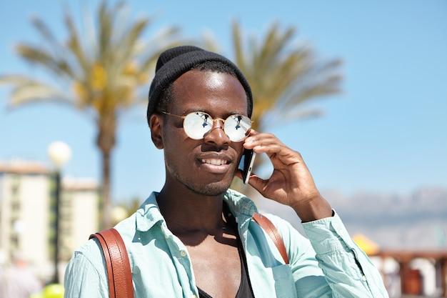 Knappe jonge hipster gekleed met telefoongesprek