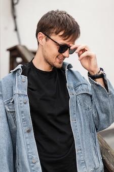 Knappe jonge hipster man met een schattige glimlach maakt zonnebril buitenshuis recht. aantrekkelijke man in een trendy denim jasje in een zwart t-shirt poseren op straat in de buurt van een vintage gebouw. trendy kleding