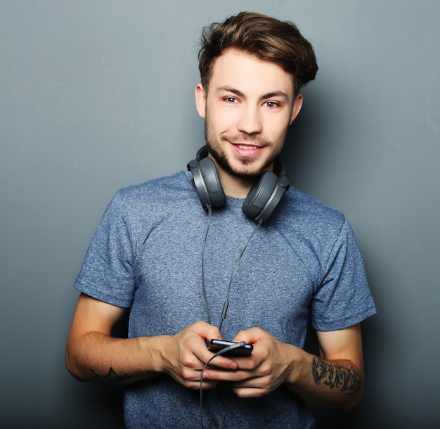 Knappe jonge hoofdtelefoons dragen op zijn hals en mens die wh glimlachen