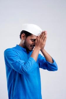 Knappe jonge indiase man met namaste of welkom gebaar, geïsoleerd op een witte achtergrond