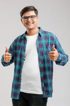 Knappe jonge indische mens die omhoog geïsoleerde dreunen toont