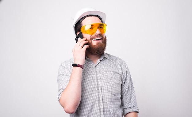Knappe jonge ingenieur helm dragen en praten over smartphone met iemand