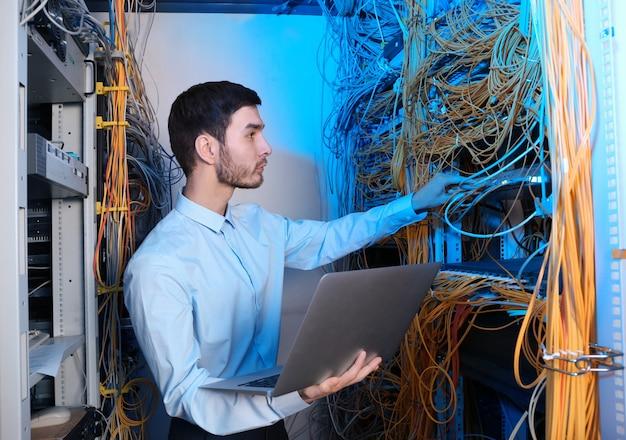 Knappe jonge ingenieur met laptop in serverruimte