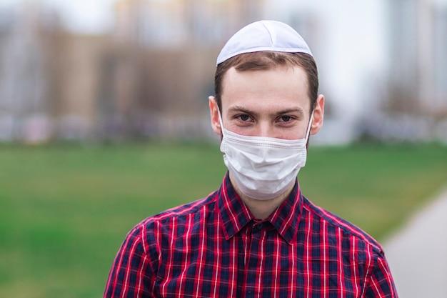 Knappe jonge joodse man in traditionele joodse mannelijke hoofdtooi, hoed, boem of jiddisch op hoofd. man in medische masker op zijn gezicht. coronavirus, virus pandemie concept. covid-19
