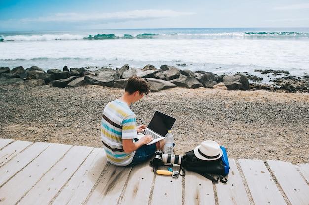 Knappe jonge kerel de fotograaf die met laptop op het strand werkt