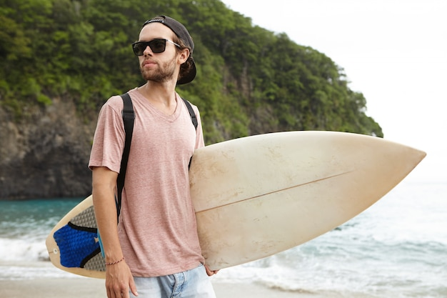 Knappe jonge kerel die surfplank in het strand draagt