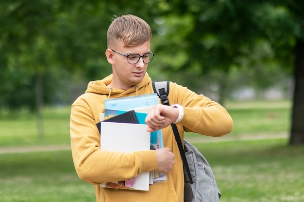 Knappe jonge kerel, drukke universiteit of student of leerling met boeken, schoolboeken en rugzak in glazen die zijn polshorloge bekijken, haastig tijd controleren, zich haasten naar lessen, examens. geen tijd.